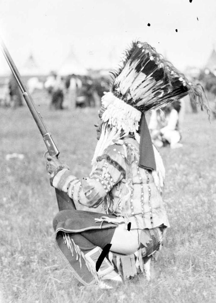 Černonožský válečník se stojatou čelenkou na dobové fotografii.