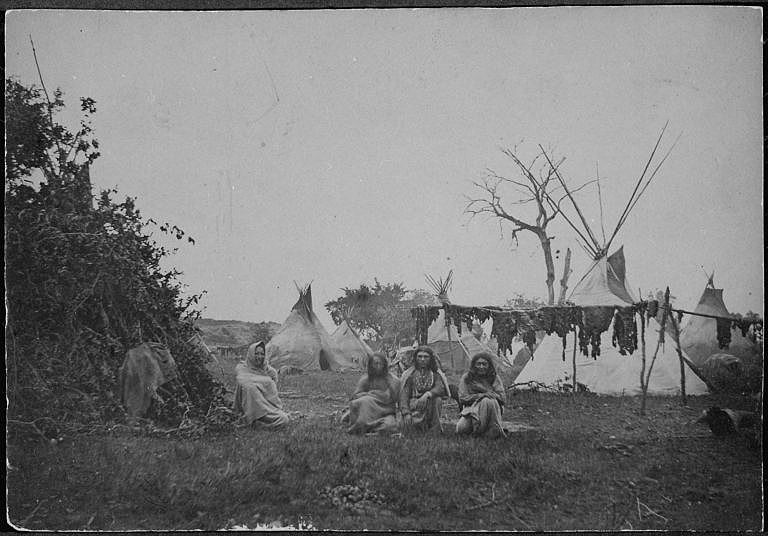 Vesnice Komančů na dobové fotografii z roku asi 1870. Na sušácích se suší bizoní maso. Po velkém a úspěšném lovu byly indiánské tábory plné takových sušáků a sušily se na nich tuny masa.