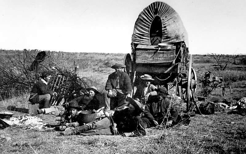 Dobová fotografie týmu lovců bizonů v poli.
