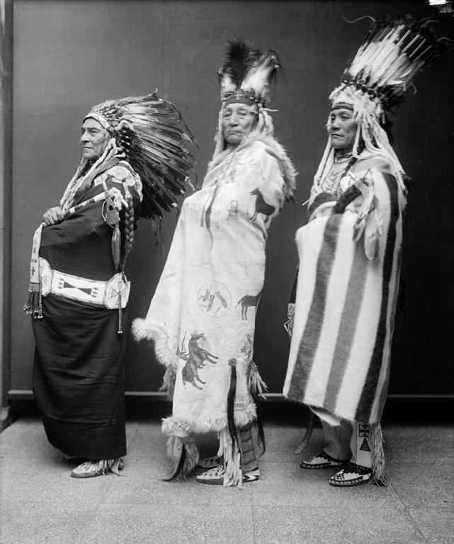 Náčelníci Černonožců. Náčelník vlevo má čelenku klasického typu zatímco náčelníci vpravo mají stojaté.