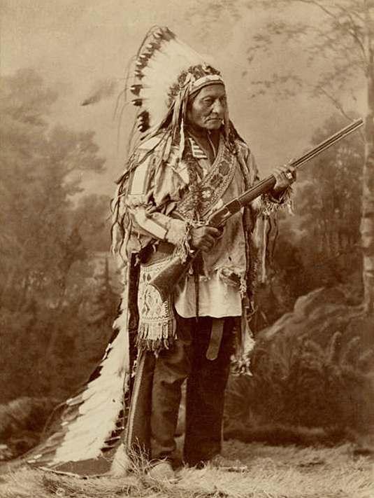 Náčelník hunkpapských lakotů Sedící býk v krásné čelence z orlích per. Vlečka sahá až na zem.