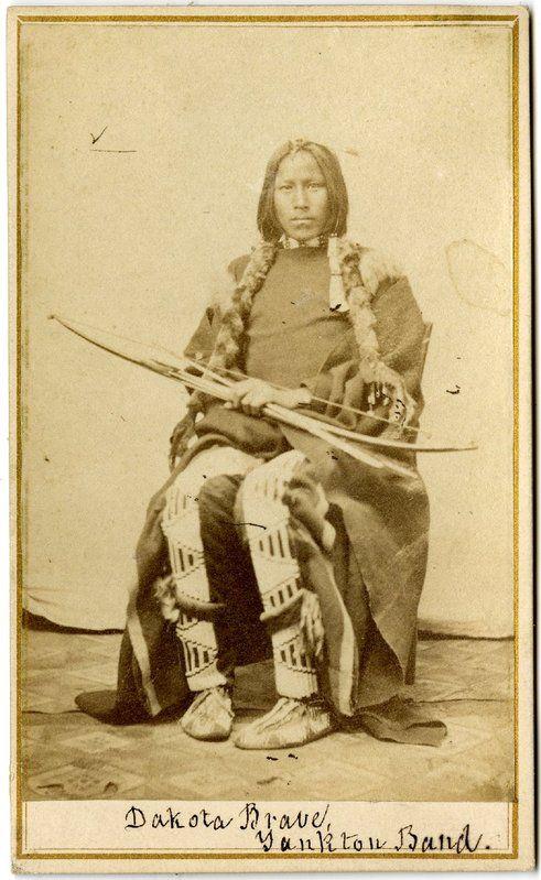 Válečník kmene Janktonských Dakotů se svým lukem na dobové fotografii.