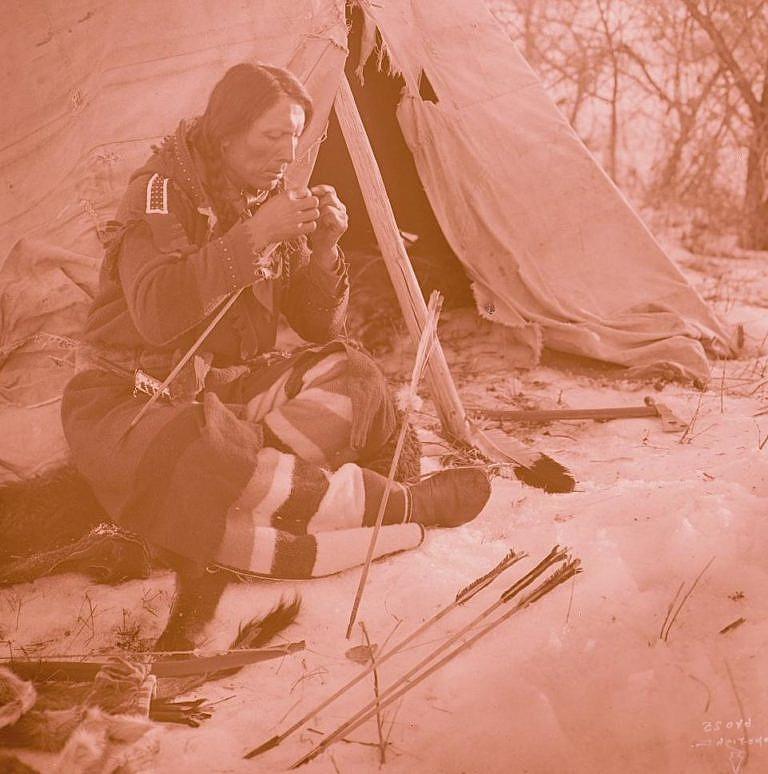 Výrobce šípů z kmene Vran při práci. Fotografie Richard Throssel. Výroba luků i šípů bylo specializované řemeslo, kterým se v každém kmeni zabývali odborníci. Ostatní si jejich výrobky museli koupit.