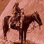 Absarocká dívka na koni v plné parádě. Na uzdě jsou dobře viditelné ozdobné řetízky