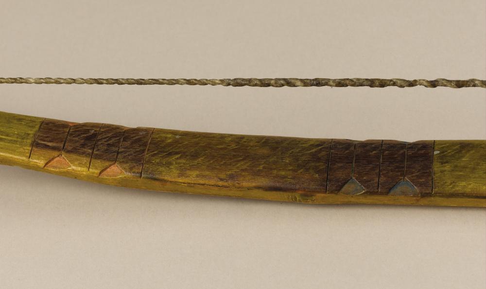 Luk z jižních plání vyrobený z maklury oranžové zdobený vyřezáváním a barvením.