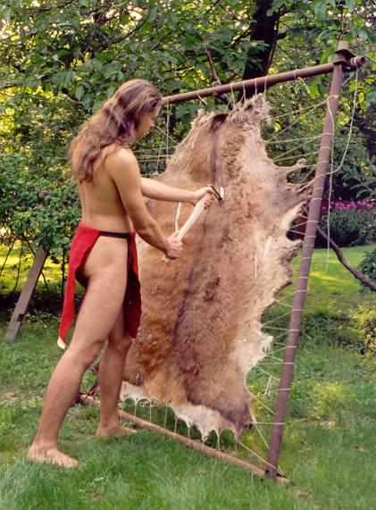 Autor článku škrábe chlupy z vysušené jelení kůže napnuté do rámu.