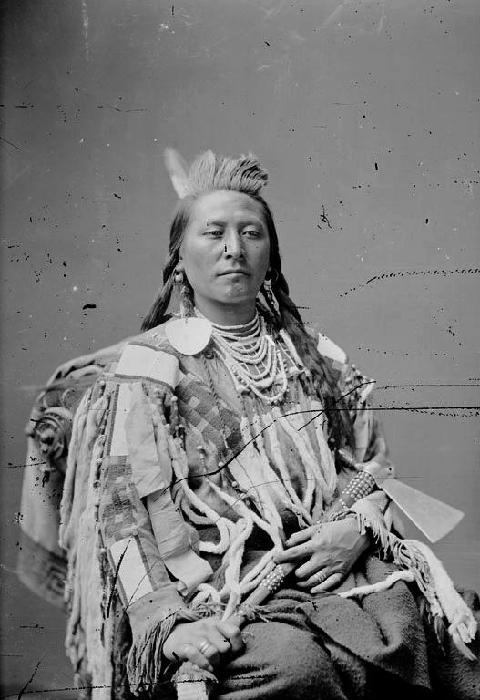 """Náčelník kmene Vran """"Mnoho úderů"""". Na sobě má halenu zdobenou korálkovanými pásy a hranostajími kožešinkami. Fotografie z 80.let 19.století."""