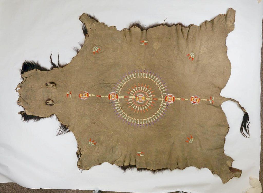 Bizoní plášť kmene Mandan. Ozdoben je quillovým pásem a symbolem slunce či péřové čelenky namalovanými hlinkou. Všimněte si typických švů. Pennsylvania museum.
