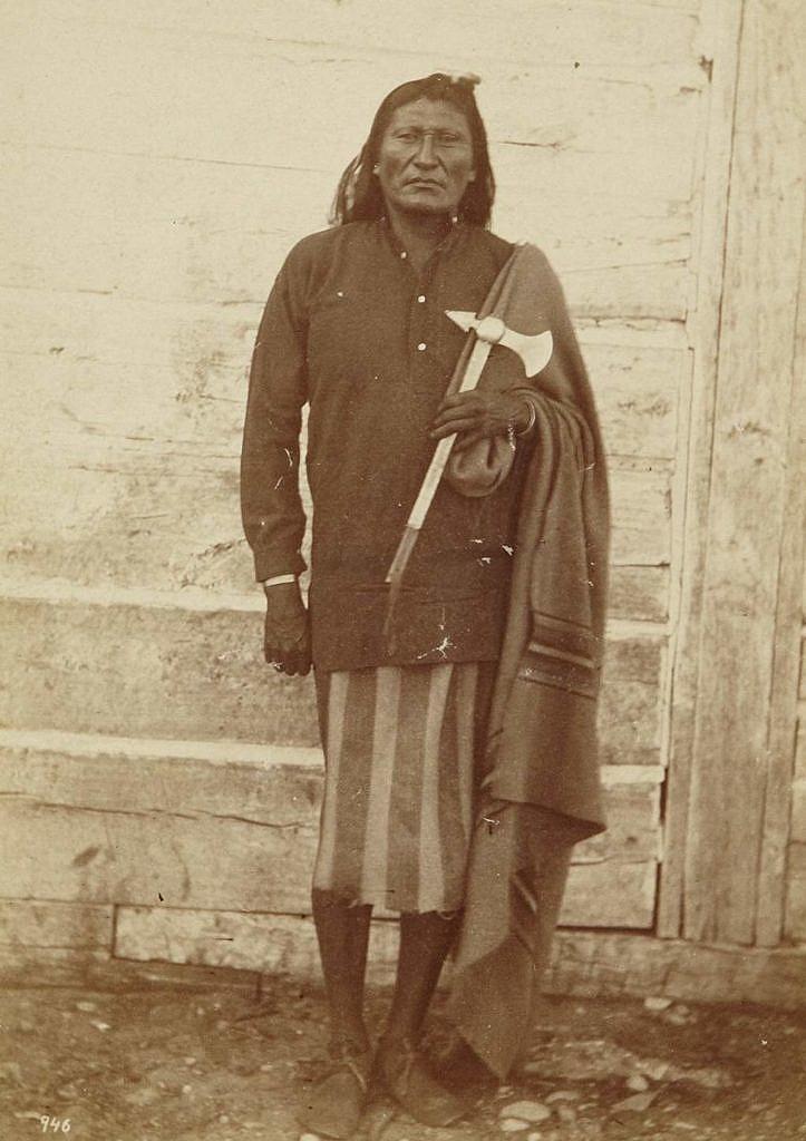 Sedí uprostřed země, náčelník kmene Vran. Jeho bederka je vyrobena z vlněné deky (ne Hudsons Bay). Fotografie Williama Jacksona z roku 1871.