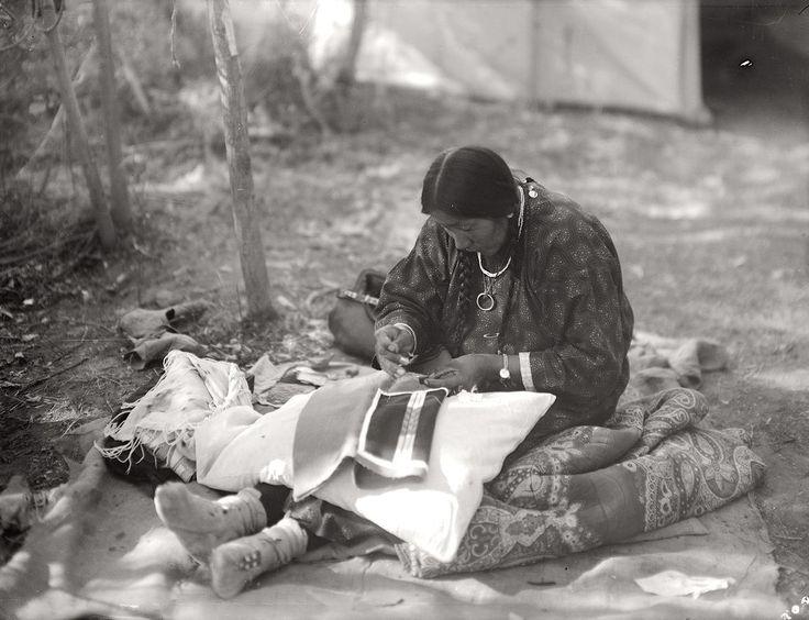 Žena kmene Vran vyrábí oblečení pro svého manžela. Výroba oblečení byla výhradně ženská práce.