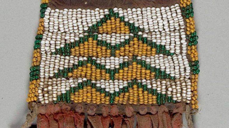 Váček na ocílku. NMNH. Trojúhelníčky jsou vyšity kukuřicovými seed beads korálky se zeleným lemováním.