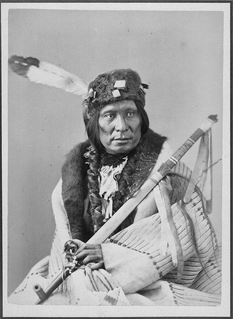 Válečník kmene Propíchnutých nosů kouřící dýmku na dobové fotografii.