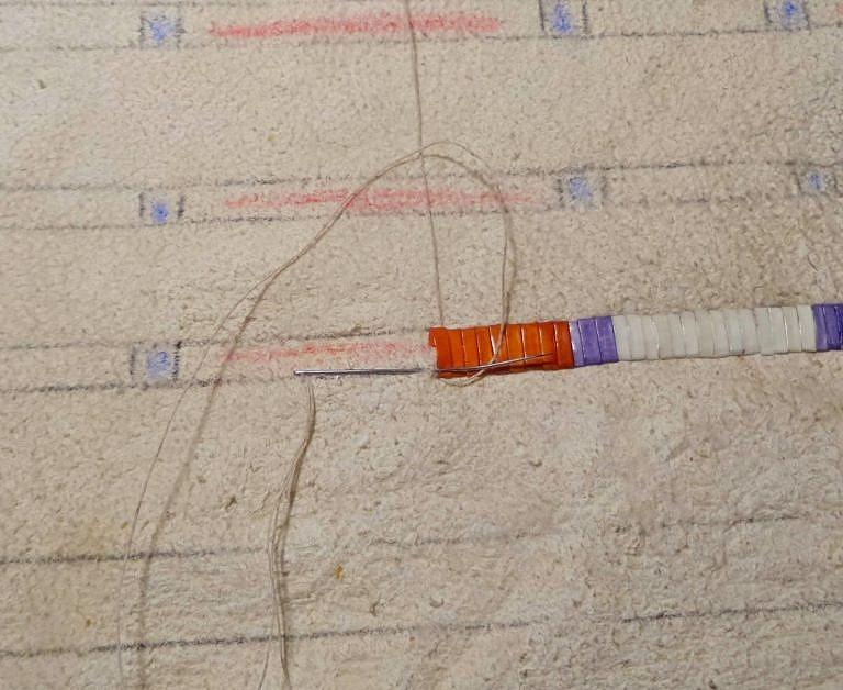 Jeden ještě nedokončený řádek podvlékaného stehu. Jehla se šlachou se většinou pouze propichovala pod povrchem, ne skrz.