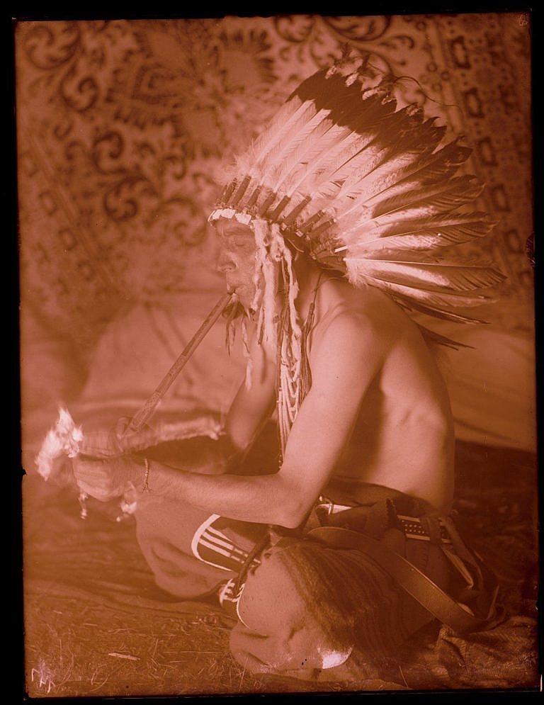 """Válečník kmene Vran jménem """"Krásný na kopci"""" kouří dýmku na dobové fotografii Richarda Throssela."""