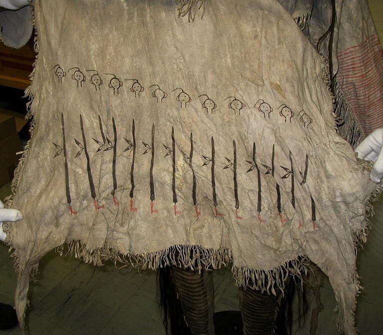 Symboly dýmek namalované na válečnou halenu. Každá dýmka symbolizuje vedení jedné válečné výpravy. Hlavy nad nimi zřejmě symbolizují zabité nepřátele.