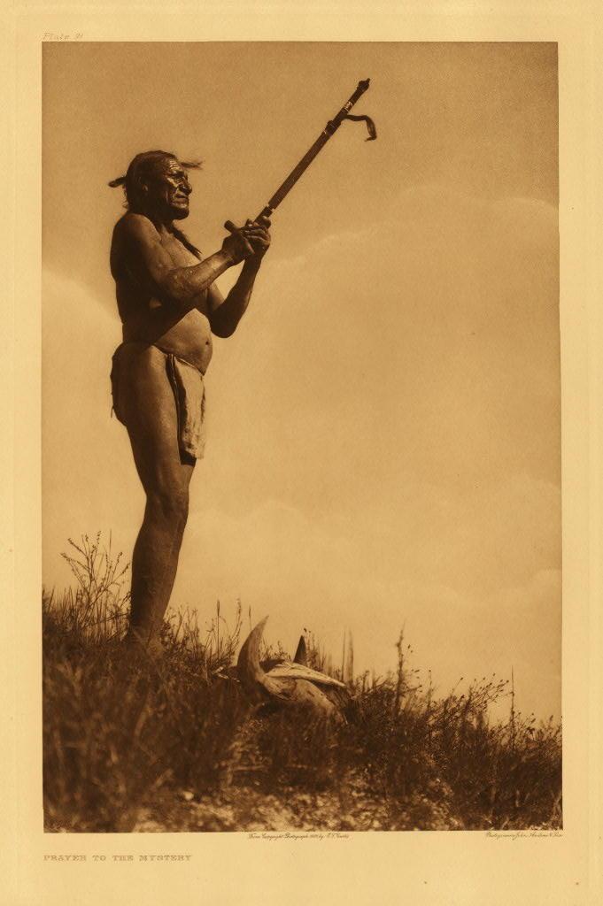 """Lakotský """"svatý muž"""" se modlí se svou dýmkou. Fotografie E.Curtis."""