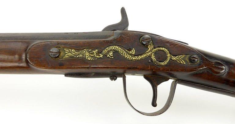 Northwest trade gun neboli severozápadní komerční puška. Detail mosazného odlitku hada nebo draka přišroubovaného na protistranu zámkové desky. Jedná se o typický poznávací znak této zbraně.