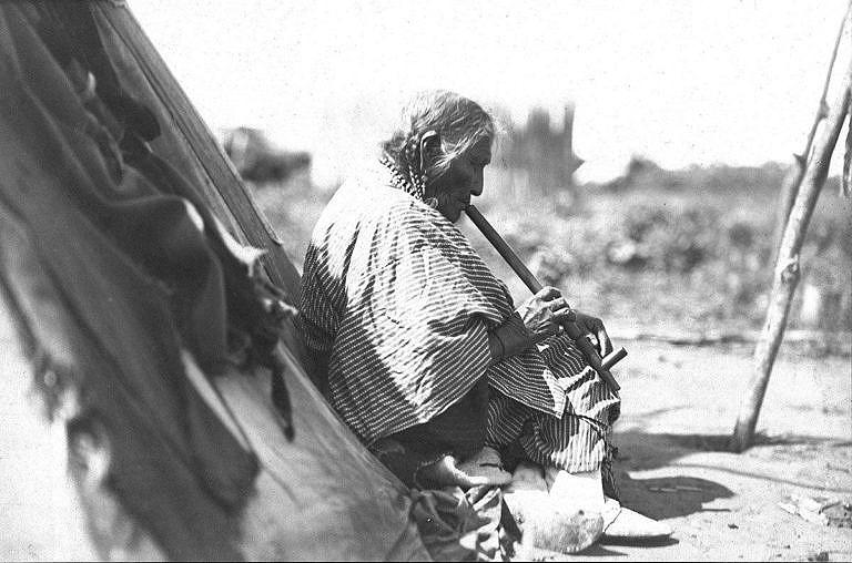 Stará žena Rudý korálek kouří dýmku. Fotografie George Grinnell.