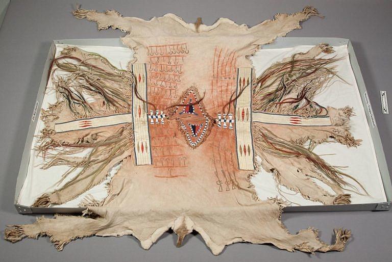 Válečná halena kmene Mandan (asi) ze sbírky G.K.Warrena z 50. let 19. století. Je vyrobená z kůží ovce tlustorohé a vyšitá ursoními ostny. Chlupy v oblasti ocasu a zadních nohou jsou na kůži stále viditelné. Jedná se o typický ozdobný prvek.