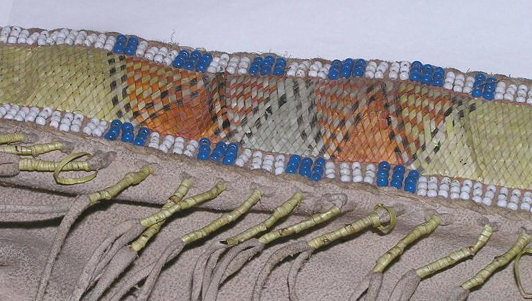 Pás z válečné haleny kmene Vran. Vyšitý je složitým proplétaným stehem, kde se ostny proplétají v diagonálním sklonu.
