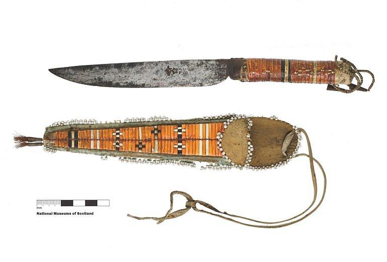 """Skaplovací nůž, tzv. """"scalper"""" francouzské výroby. Indián si upravil ručku do kulatého průřezu a jeho žena ji ozdobila ursoními ostny. K noži je i pouzdro, opět zdobené urosními ostny, které indián nosil na krku. Takováto pouzdra na nůž na nošení kolem krku byla typická pro indiány z východních lesů. National Museum of Scotland."""