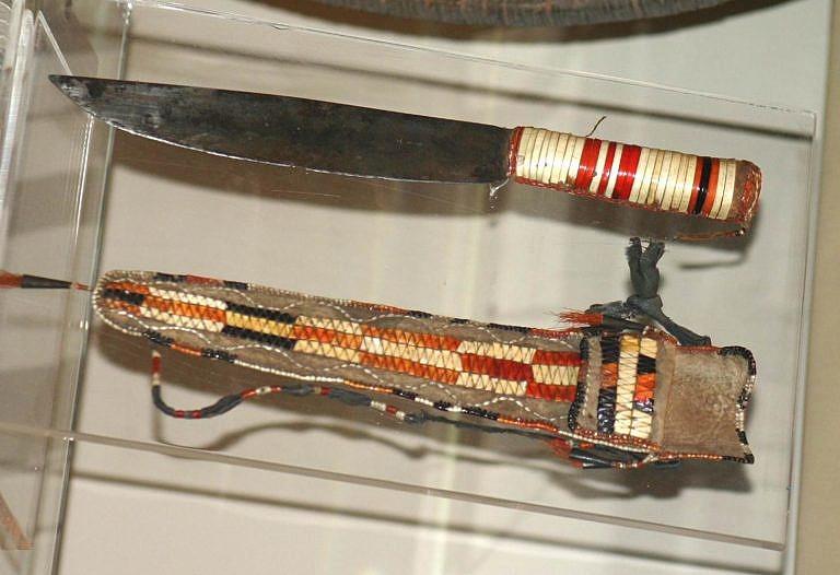 """Typický """"scalper"""", pravděpodobně francouzského původu. Indián si upravil a dozdobil ručku ursoními ostny, aby více odpovídala jeho představám. K noži je i pouzdro, které se nosilo kolem krku. British museum, Londýn."""
