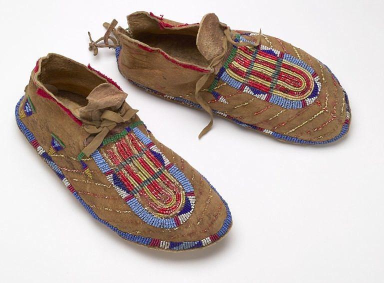 Dvoudílné mokasíny. Ornamenty na nártu jsou vyšity technikou omotávaných žíní (dvojlinka). Baťa shoe museum, Toronto.