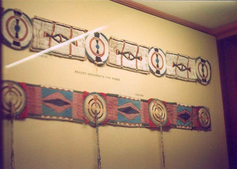 Pásy na deku či plášť. U spodního pásu jsou pouze rozety jsou vyvedeny omotávanými žíněmi, rovné mezikusy jsou vyšity korálky seed bead. Kmen Jakima, Field museum.