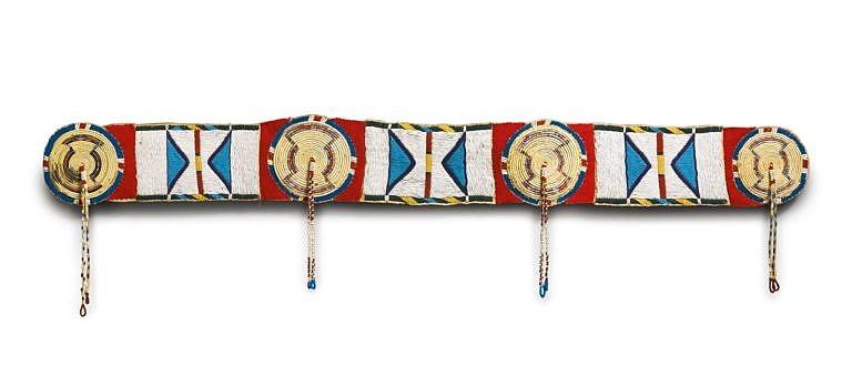 Vyšívaný ozdobný pás na bizoní plášť nebo deku. Rozety jsou vyšity technikou omotávaných koňských žíní. Hranaté mezikusy jsou vyšity korálky. Sothebys auction.