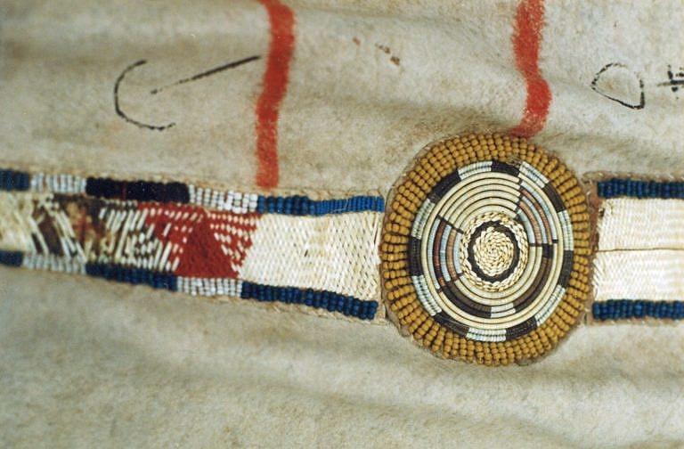 Detail bizoního plášťě s ozdobným pásem. Rozety jsou vyšity ostny na omotávaných žíních zatímco hranaté mezikusy jsou vyšity technikou proplétaného quillu. Bernisches historisches museum.