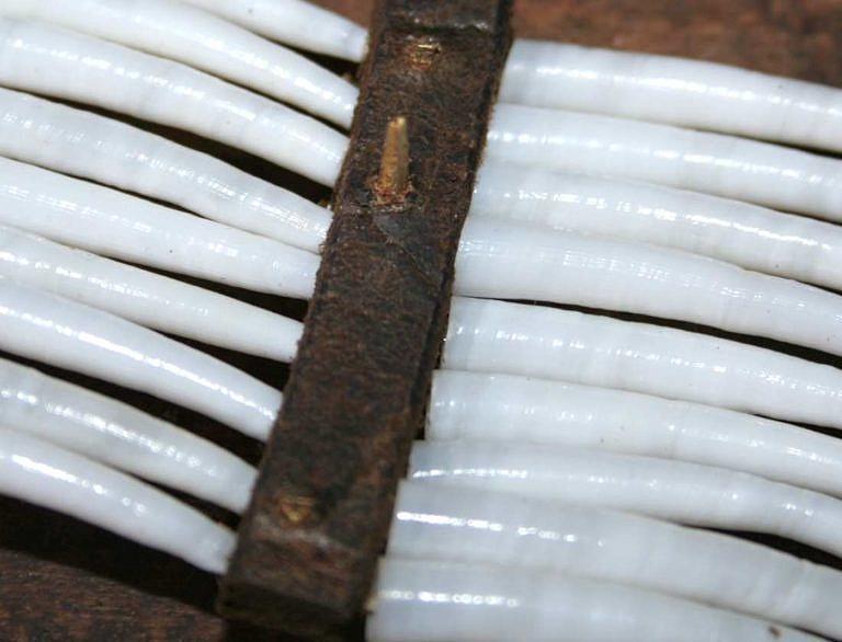 Nožička mosazného hřebu čnějící na rubové straně.