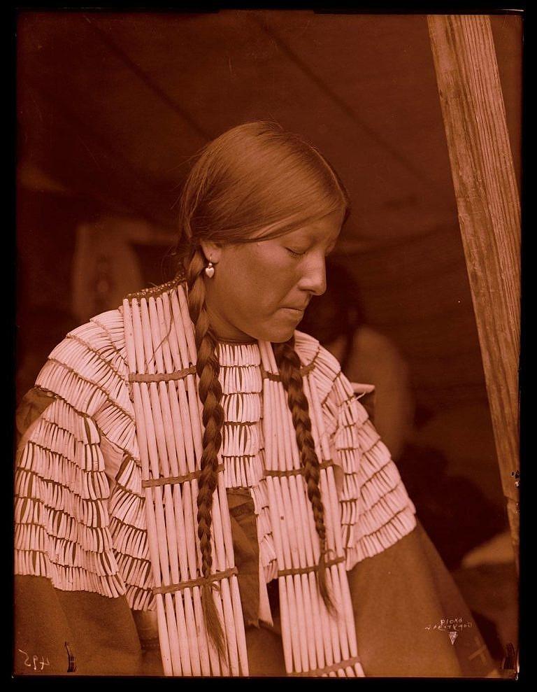 Lakotská žena na fotografii R.Throssela. Na sobě má šaty, jejichž celé sedlo je pošito kelnatkami.