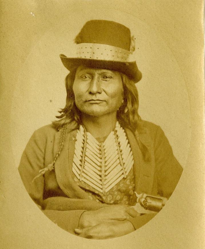 Náčelník Komančů Šedé legíny na fotografii z roku 1870. Na sobě má čtyřřadou kosticovou náprsenku s kosticemi ležícími šikmo. Takové náprsenky jsou typické pro jižní pláně.