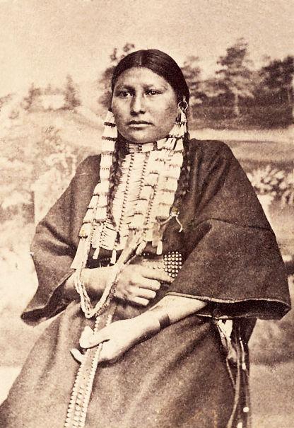 Žena z kmene Lakotů s náprsenkou z kelnatek.