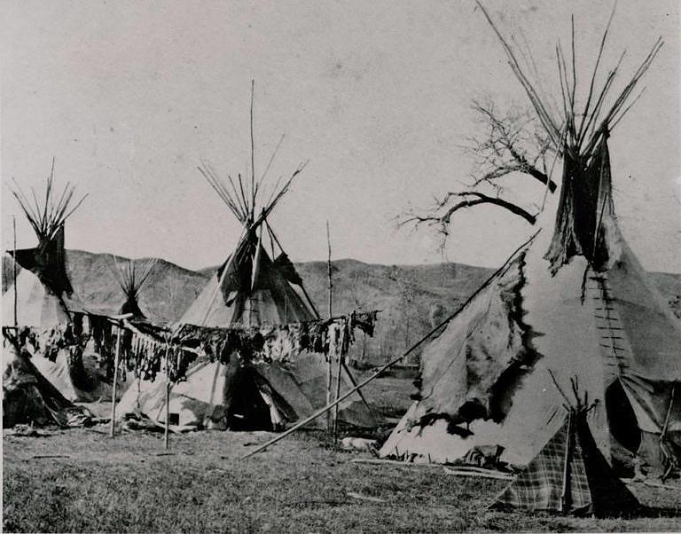 Týpí Šajenů na řece Yellowstone. Dobová fotografie ze 70. let 19. století. Týpiové tyče jsou přiměřeně dlouhé.