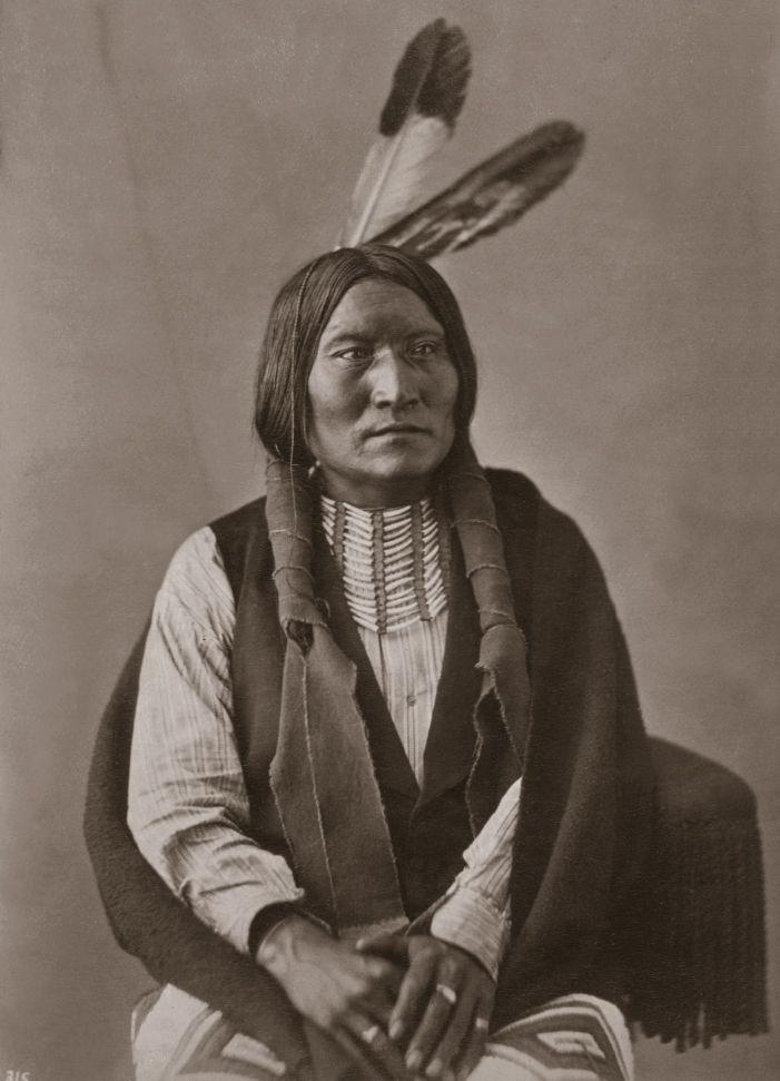 Špinavá tvář z kmene oglalských lakotů s kelnatkovou náprsenkou. Fotografie z toku 1872.