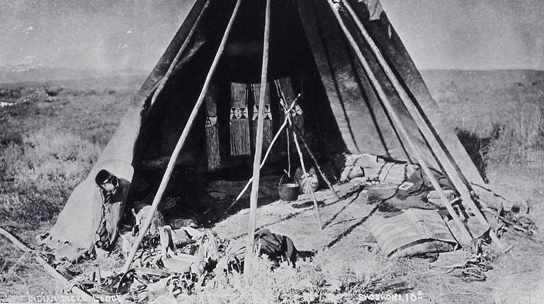 Interiér týpí kmene Šošonů na dobové fotografii. Kostra z tyčí je odhalená.