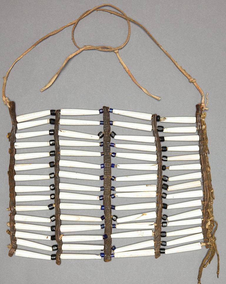 Náprsenka vyrobená z kostic z mušloviny. Je čtyřřadá a pravděpodobně pochází z oblasti jižních plání. Prakticky všechny kostice jsou přepůlené (původně byly dvojnásobně dlouhé). Heritage auctions.