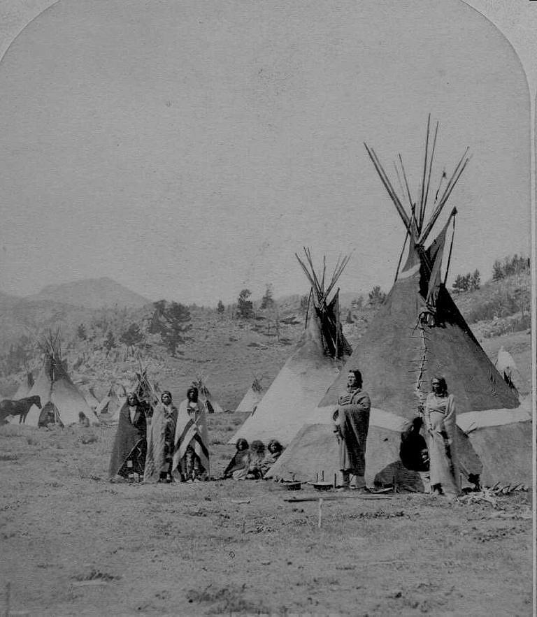 Tábor Šošonů na dobové fotografii z konce 60. nebo začátku 70. let 19. století. Týpí jsou ještě z bizoních kůží. Vchody týpí směřují na východ a zřejmě je bezvětří nebo fouká západní vítr, takže kouřové chlopně jsou přiměřeně otevřené.