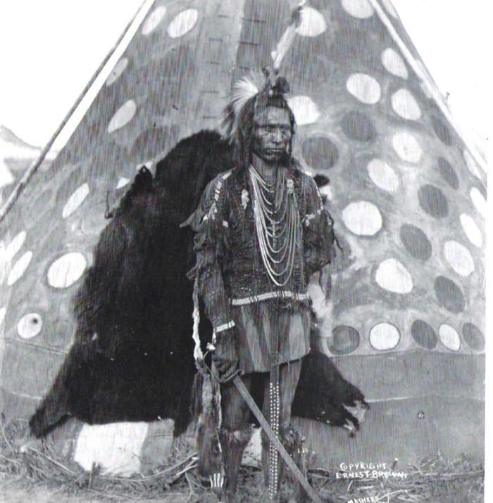 Dobová fotografie týpí kmene Černonožců s dveřmi vyrobenými z kožešiny medvěda Baribala.