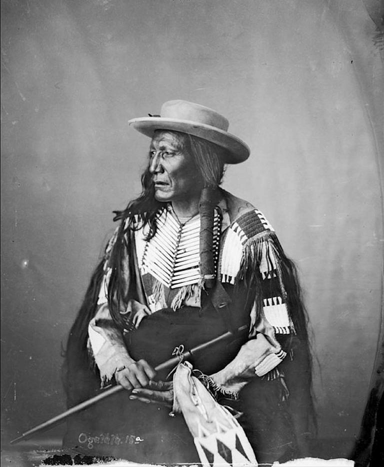 Vysoký vlk z kmene oglalských Lakotů s typicky dvouřadou náprsenkou z centrálních plání. Fotografie pochází z roku 1872.