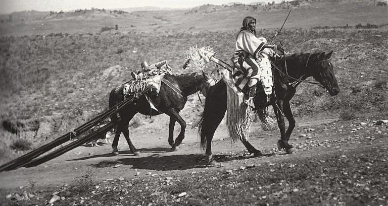 Indiánka kmene Vran na dobové fotografii. Vede nákladního koně, který má k sedlu připevněné týpiové tyče, vždy na kěždé traně stejný počet tyčí. Tyče se k sedlu přivazovaly za tenčí konec a silnější konce se táhly po zemi, címž se obrušovaly do špičky.