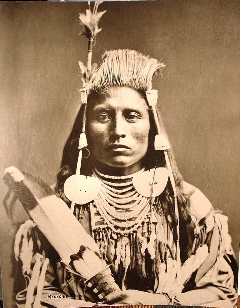 Kouzelná Vrána, mladý válečník kmene Vran na dobové fotografii roku 1880. Jeho motýlci jsou novější variantou, závěsy jsou vyrobeny z kostic.