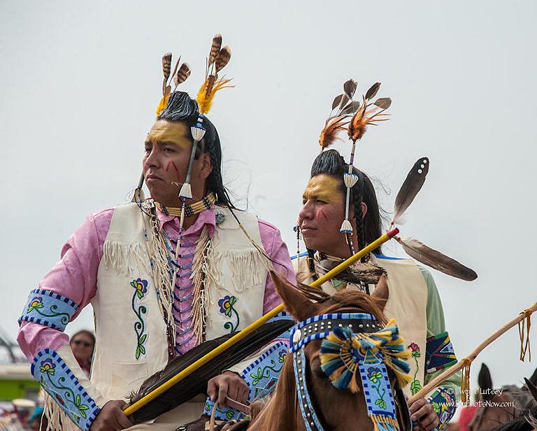Dva Vraní indiáni na slavnosti Crow fair v roce 2015. Oba mají na sobě motýlky, i když v poněkud pozměněných proporcích, oproti původní verzi z Catlinových a Bodmerových obrazů.