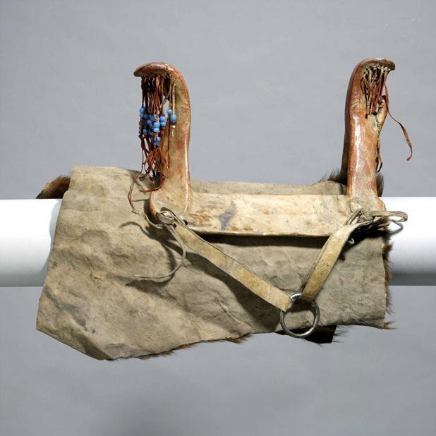 Ženské dřevěné sedlo vypodložené podsedlovou deku ve formě kusu bizoní kožešiny. Royal Ontario Museum.