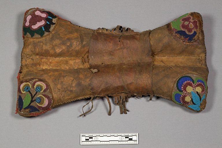 Polštářové sedlo kmene Kríů. Jeho rohy jsou zdobeny korálkovou výšivkou s květinovým motivem. Taková sedla vyráběli i Odžibwejové, ovšem ti většinou používali, na rozdíl od Kríů jako podklad korálky bílé barvy. Sbírka NMNH.
