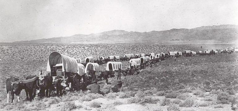 Karavana krytých vozů s evropskými imigranty míří na západ přes Velké pláně.
