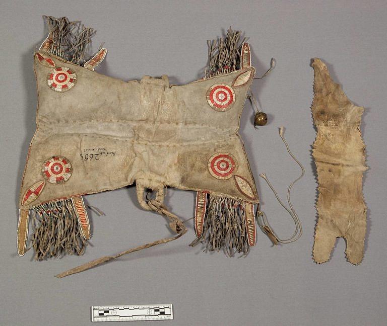 Polštářové sedlo kmene Černonožců, získané před rokem 1850. Rohy jsou zdobené rozetami a kosočtverci vyšitými ursoními ostny, což je pro ranná černonožská sedla typické.