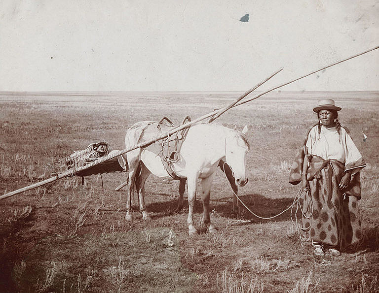 Žena ze severních plání na dobové fotografii. Její kůň má na sobě nákladní tetřívkové sedlo vypodložené bizoní kožešinou.