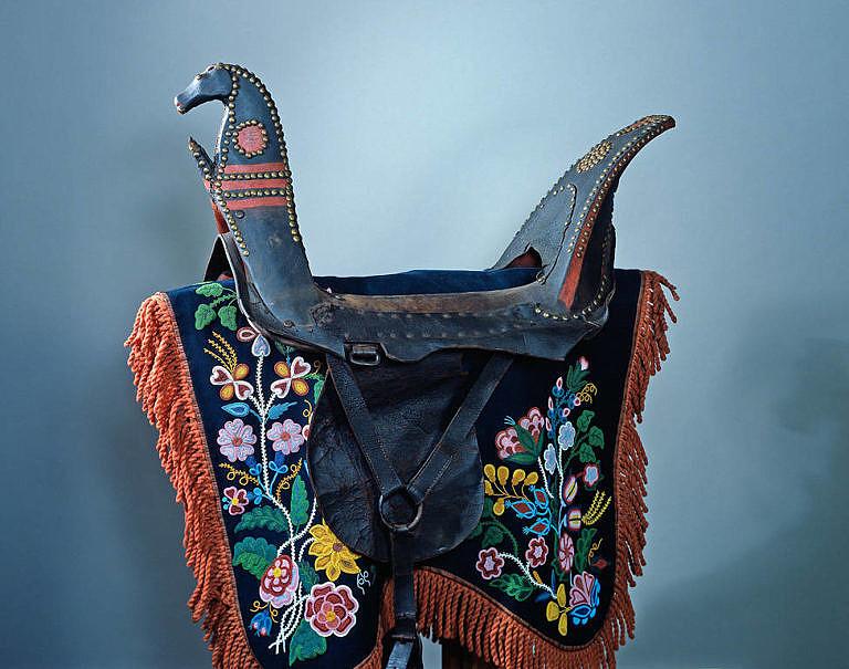 Podsedlová deka kmene prérijních Odžibwejů. Vyrobená je z vlněné látky a pošitá krásnou florální výšivkou. Získána byla v roce 1874. NMNH.